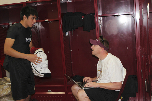 Senior linebacker Johnny Rodgers logs in his Guardian Cap, and other equipment, with Faith Lutheran assistant coach Jake Kothe. (W.G. Ramirez/Las Vegas Review-Journal)