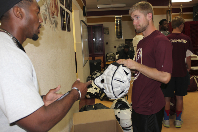 Faith Lutheran head coach Vernon Fox and assistant coach Grant Rolfsmeier chat while handing out equipment – including Guardian Caps – prior to the Crusaders leaving for football camp at Fresn ...