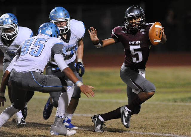 Cimarron's Derek Morefield (5) looks for running room around Centennial's Andre Diller (85) during a football game at Cimarron-Memorial High School in Las Vegas Thursday, Oct. 24, 2013. Morefield  ...