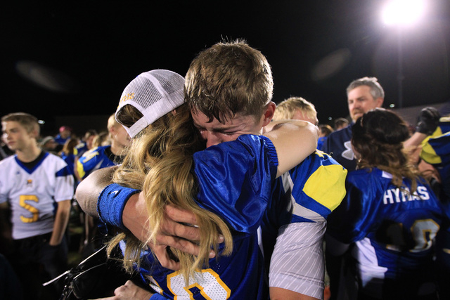 Moapa Valley quarterback Zach Hymas gets a big hug from his mother Becky Hymas after the Pirates defeated Desert Pines 42-36 in overtime for the Division I-A state title on Saturday. Hymas passed  ...