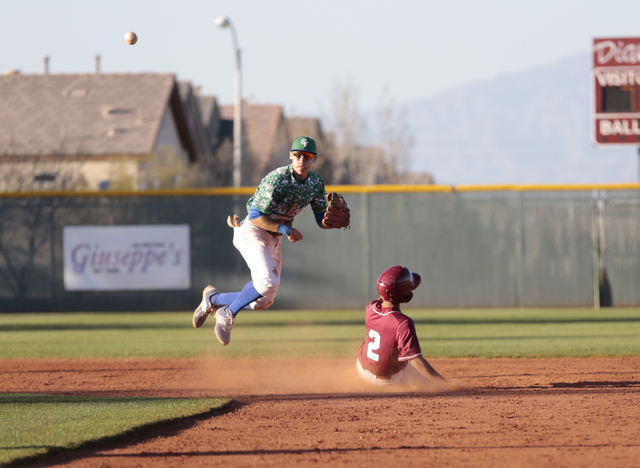 Green Valley senior Jarod Penniman (4) throws towards first base after getting Desert Oasis senior Chris Van Kuren (2) at second base during the championship game of the Lions Kickoff Tournament a ...