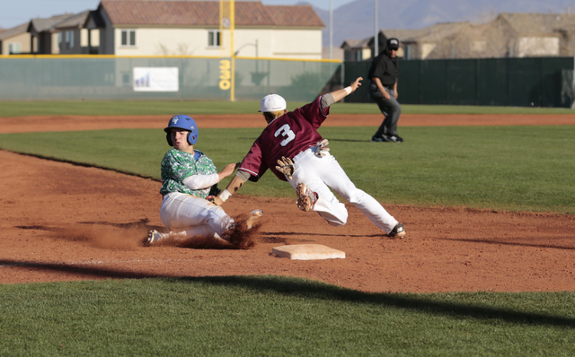 Green Valley sophomore A.J. Amelburu (4) slides into third base and is tagged by Desert Oasis senior Caeden Marin (3) during the championship game of the Lions Kickoff Tournament at Desert Oasis o ...