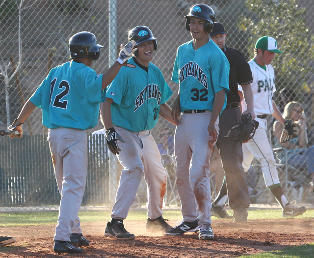 Silverado's Alex Grafiada (12), Dillon Johnson (21) and Nick Kawano (32) celebrate Vincent Taormina's game-winning hit against Palo Verde on Friday. Silverado won the game 11-8. (Chase Stevens/Las ...