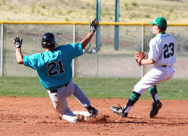 Silverado's Dillon Johnson (21) slides safely into second base as Palo Verde's Mitchell Rathbun (23) waits for the ball on Friday. Silverado won the game 11-8. (Chase Stevens/Las Vegas Review-Journal)
