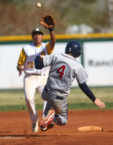 Liberty's Jay Martz (4) attemps to slide safely into second base as Rancho's Juan Cruz (12) reaches to catch the ball during Saturday's game. (Chase Stevens/Las Vegas Review-Journal)