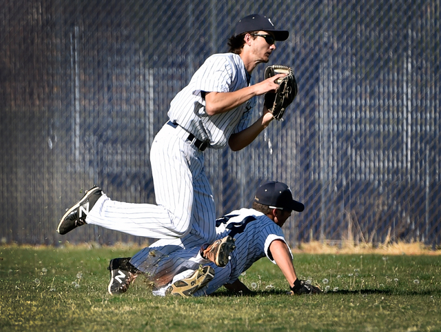 Spring Valley's Carter Lambeth, left, trips over teammate Nick Rupp after catching a fly call against Coronado during a high school baseball game at Spring Valley High School on Friday, March 20,  ...