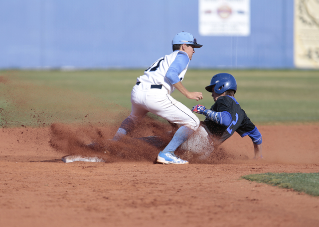 Basic High School senior Cory Wills (2) slides into second base under Centennial High School sophomore Tanner Wright (11) during a baseball game at the Centennial baseball field, 10200 W. Centenni ...