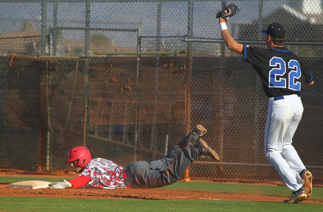 Arbor View's Nick Quintana (12) slides into first base past Sierra Vista's Nolan Kingham (22) in the seventh inning on Thursday. Arbor View won, 6-5. (Chase Stevens/Las Vegas Review-Journal)