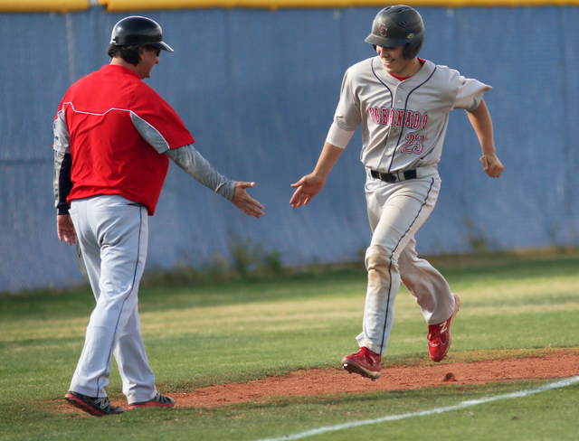 Coronado's Nate Ruiz, right, prepares to slap hands with assistant coach Rich Ebarb after Ruiz hits a home run on his way to home plate during a baseball game against Centennial at Centennial High ...