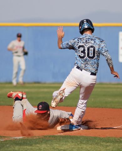 Coronado's Nicco Festa, left, dives into first base to make the out as Coronado's Travis Stevens runs during a baseball game at Centennial High School Friday, April 24, 2015, in Las Vegas. (Ronda  ...