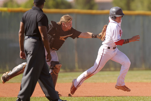Liberty's Nick Rush (5), right, is tagged out by Silverado's catcher Vincent Taormina (11) during a play in their baseball game at Liberty High School in Henderson Monday, April 27, 2015. Liberty  ...