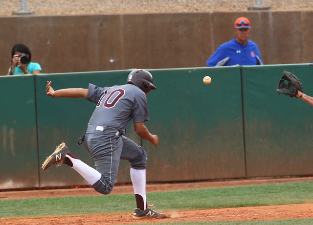 Cimarron-Memorial's Luis Flores (10) is caught in a run down between home plate and third base as Bishop Gorman's Bronson Bowe reaches to catch the ball and tag him out in the fifth inning on Mond ...