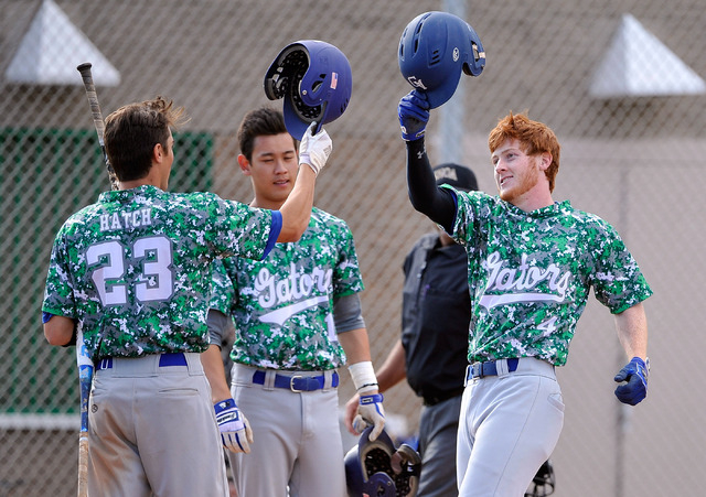 Green Valley's Keaton Smith (4) celebrates with teammates Anthony Hatch (23) and Blake Inouye after hitting a home run against Rancho on Tuesday. The Gators won, 10-4. (David Becker/Las Vegas Revi ...