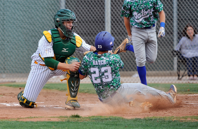 Green Valley's Anthony Hatch (23) is tagged out at home plate by Rancho catcher Zach Barnhart on Tuesday. Green Valley won, 10-4. (David Becker/Las Vegas Review-Journal)