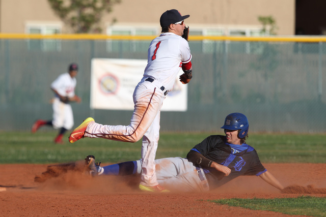 Basic's Josh McLean tries to break up a double play as Liberty second baseman Lucas Bogues is late on his throw to first during their game Thursday, March 19, 2015, at Liberty. (Sam Morris/Las Veg ...