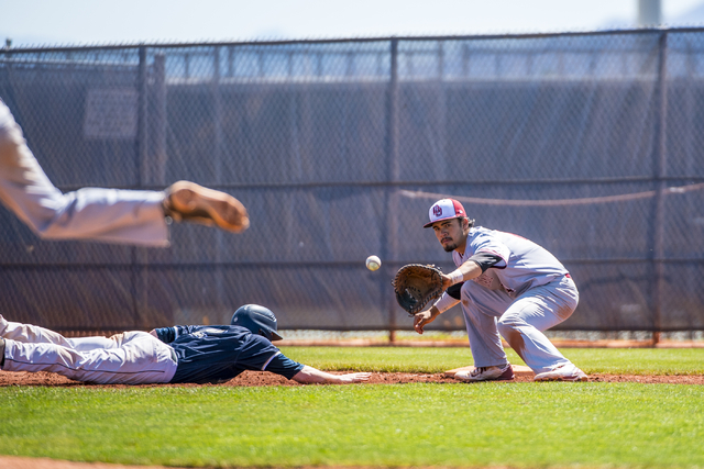 Shadow Ridge infielder Nick Erickson slides back to first base as Desert Oasis first baseman Isaiah Raiano catches the ball at Shadow Ridge High School in Las Vegas on Saturday, April 2, 2016. Eri ...
