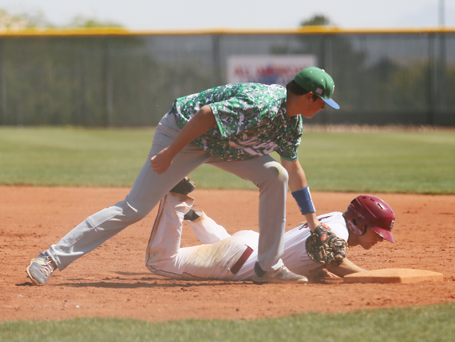 Green Valley's Drake Maningo, left, goes for an out as Dominic Paratore slides back safely to first base after leading off during a baseball game at Desert Oasis Saturday, April 11, 2015, in Las V ...