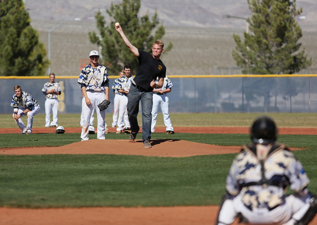 Shadow Ridge pitcher Chris Opolka, third from left, watches as Shadow Ridge graduate and Army National Guard member Jake Rooney throws the first pitch at the start of a baseball game against Palo  ...