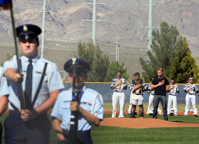 Shadow Ridge pitcher Chris Opolka, center from left, catcher Robbie Galvan and Shadow Ridge graduate and Army National Guard member Jake Rooney stand during the National Anthem before the start of ...