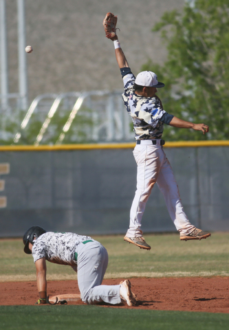Shadow Ridge's Eric Jordan, right, goes for a catch as Palo Verde's Yodai Nakamura recovers from a slide into second during a baseball game at Shadow Ridge High School Monday, April 13, 2015, in L ...