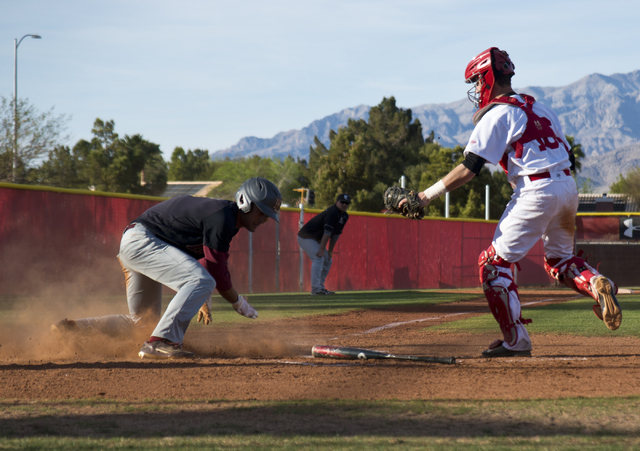 Faith Lutheran's Josh Harmonay (9) slides into home plate as Arbor View's Joe Fitzhugh (16) tries to tag him during their game at Arbor View High School in North Las Vegas on Thursday, March 10, 2 ...