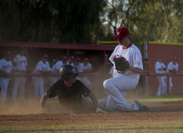 Faith Lutheran's Sagan Groaner (15) slides into home plate as Arbor View's Jaxon Sproul (28) attempts to stop him during their game at Arbor View High School in North Las Vegas on Thursday, March  ...