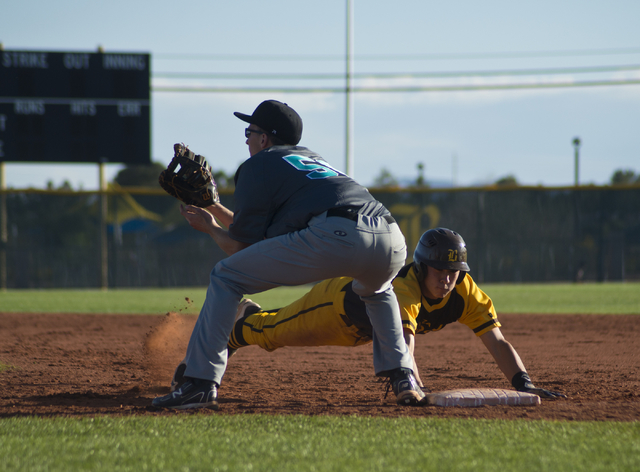 Bonanza's Micah Higa (8) dives to tag first base as Silverado's Samuel Pope (50) waits for the throw during their game at Bonanza High School in Las Vegas on Friday, March 11, 2016. Bonanza won th ...