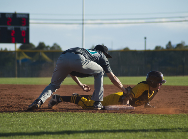 Bonanza's Micah Higa (8) dives to tag first base as Silverado's Samuel Pope (50) attempts to tag him out during their game at Bonanza High School in Las Vegas on Friday, March 11, 2016. Bonanza wo ...