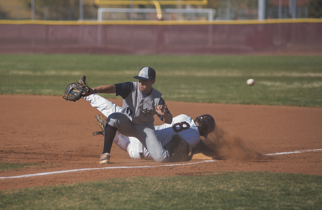 Faith Lutheran's Alex Giuliani (8) slides back to first base as Spring Valley's Jack Sellinger (17) misfields the ball during their baseball game played at the Faith Luthern baseball field in Las  ...