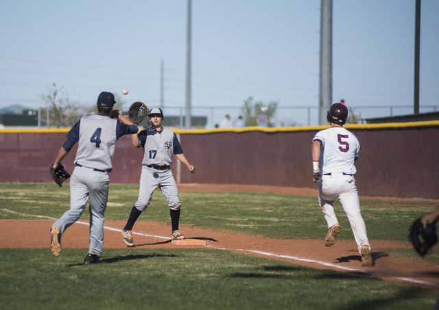 Faith Lutheran's Greg Sylvester (5) hussles to first base as Spring Valley's Bryce Bullock (4) throws the out to Jack Sellinger (17) during their baseball game played at the Faith Luthern baseball ...