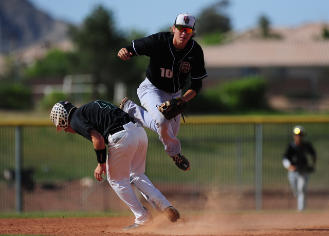 Palo Verde base runner Asher Bouldin (4) interferes with Desert Oasis shortstop Bryson Stott while Stott tries to turn a double play in the third inning of their prep baseball game at Palo Verde H ...