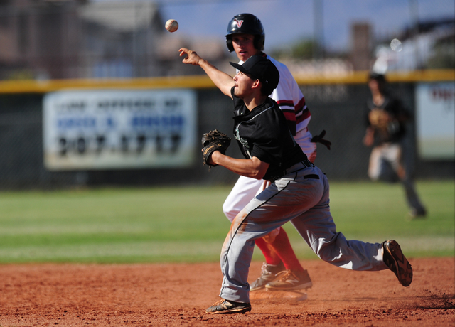 Rancho shortstop Braulio Santiaguin turns a double play as Las Vegas baserunner Ryan Freimuth slides to second base in the third inning of their prep baseball game at Las Vegas High School Tuesday ...