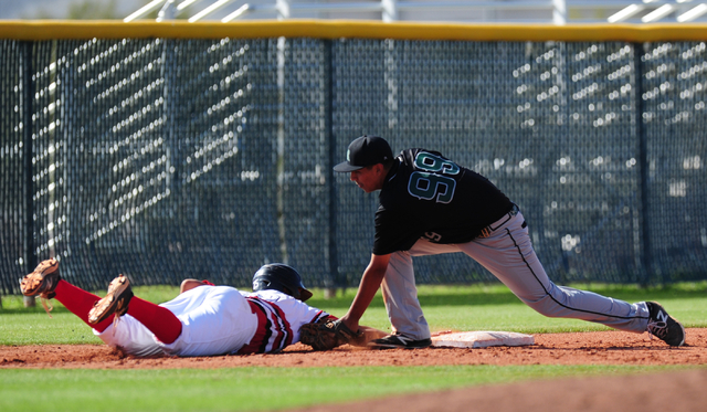Rancho third baseman Jimmy Gamboa tags Las Vegas baserunner Antonio Gaxiola to complete a double play after Gaxiola overran third base in the third inning of their prep baseball game at Las Vegas  ...
