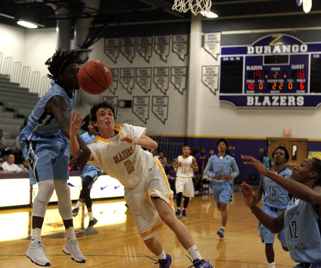 Durango guard Alex Tarkanian center shoots between Canyon Springs forward Kajuan Casey (5) and Canyon Springs forward Maurice Hunter (12) in the first quarter on Tuesday. Canyon Springs won, 61-57 ...