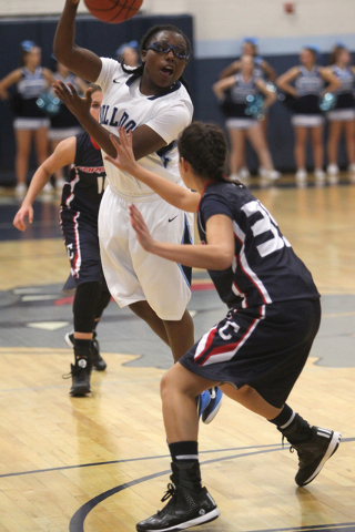 Centennial guard Tanjanae Wells passes over Coronado guard Taylor Tyrell in the second quarter on Wednesday. Wells had 12 points and six rebounds to help Centennial win, 72-41. (K.M. Cannon/Las Ve ...