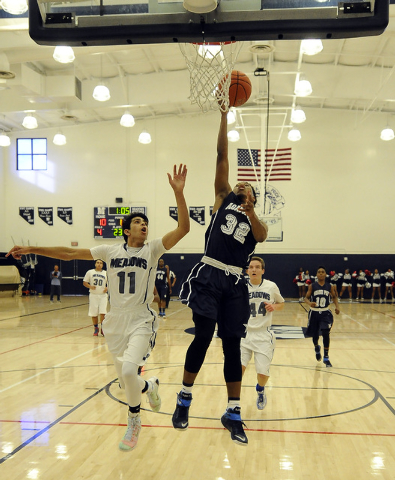Agassi Prep forward Kenneth Hatano (32) scores on a layup as The Meadows School guard Asheesh Chopra (11) defends in the first quarter on Saturday. Hatano scored 15 points in a 68-63 Agassi Prep w ...