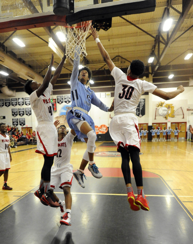 Canyon Springs guard Zaahid Muhammad, center, goes up for a layup while being guarded by Las Vegas High forward Will Loche (44), guard Devon Colley (12) and forward Tyler Bey (3) on Wednesday. Las ...