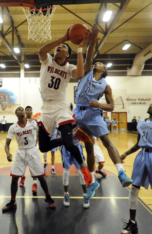 Las Vegas High forward Tyler Bey (30) attempts a layup as Canyon Springs forward Maurice Hunter (12) defends during the third quarter on Wednesday. Bey had 25 points in a 77-51 Las Vegas win. (Jos ...