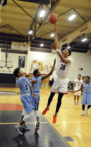 Las Vegas forward Tyler Bey makes a field goal in front of Canyon Springs gaurd Zaahid Muhammad, left, and guard D'Quan Crockett, during the third quarter on Wednesday. Bey had 25 points in a 77-5 ...
