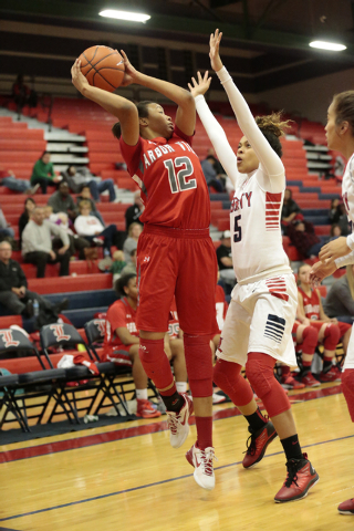 Arbor View's Ariona Gill (12) looks to pass the ball over Liberty's Jaelyn Royal (5) during the second half of their game Monday at Liberty. Gill scored seven points, but the Patriots topped Arbor ...