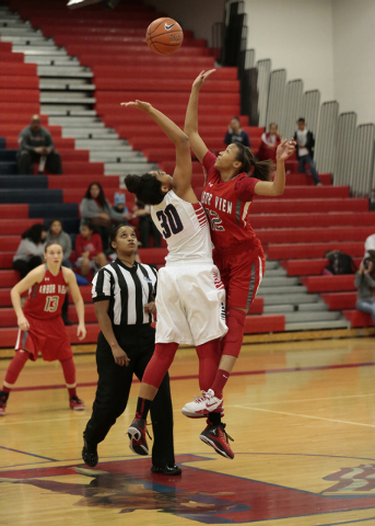 Liberty's Paris Strawther (30) and Arbor View's Ariona Gill (12) reach for the ball during the opening tip of Monday's game at Liberty. Strawther scored her 1,000th career point in the Patriots' 5 ...