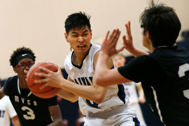 Calvary Chapel's Marior Munda, center, keeps a ball away from Mountain View's Daniel Reyes, right, during the second half of a basketball game at Calvary Chapel Christian High School in Las Vegas, ...