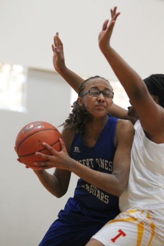 Desert Pines' Brianna Fitzgerald (24) looks for an opening against Tech's Patrice Thomas (31) during their game in the Lady Wolves Holiday Tournament on Tuesday. Fitzgerald scored four points as D ...