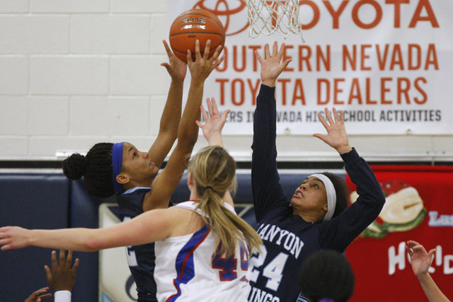 Canyon Springs guards Mia Moss, left, and Daijhan Cooks grab a rebound from Reno center Mallory McGwire during their Las Vegas Holiday Classic tournament game Saturday. (Sam Morris/Las Vegas Revie ...