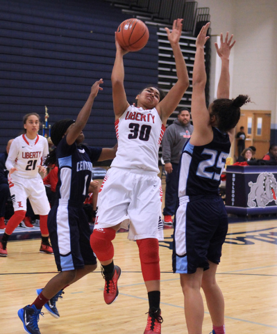 Liberty forward Paris Strawther drives between Centennial guards Pam Wilmore, left, and Karina Brandon during the championship game of the Las Vegas Holiday Classic on Tuesday. Centennial won the  ...