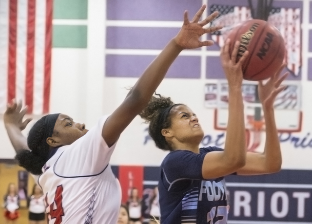 Foothill's Rae Burrell (12) drives past Liberty's Dre'una Edwards (44) during the Falcons' road matchup with the Patriots  on Monday, Jan. 9, 2017, at Liberty High School, in Las Vegas. Benjamin H ...
