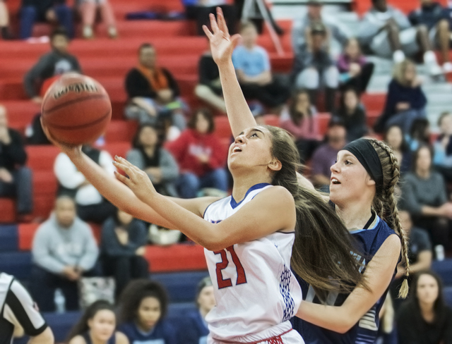 Liberty's Kaily Kaimikaua (21) slashes to the rim past Foothill's Kylie Vint (11) during the Patriots home matchup with the Falcons on Monday, Jan. 9, 2017, at Liberty High School, in Las Vegas. B ...