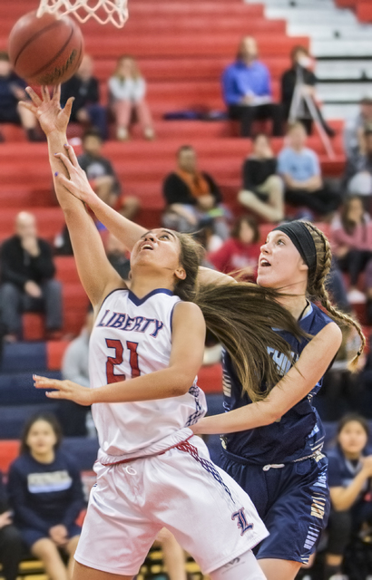 Liberty's Kaily Kaimikaua (21) shoots a contested layup over Foothill's Kylie Vint (11) during the Patriots home matchup with the Falcons on Monday, Jan. 9, 2017, at Liberty High School, in Las Ve ...