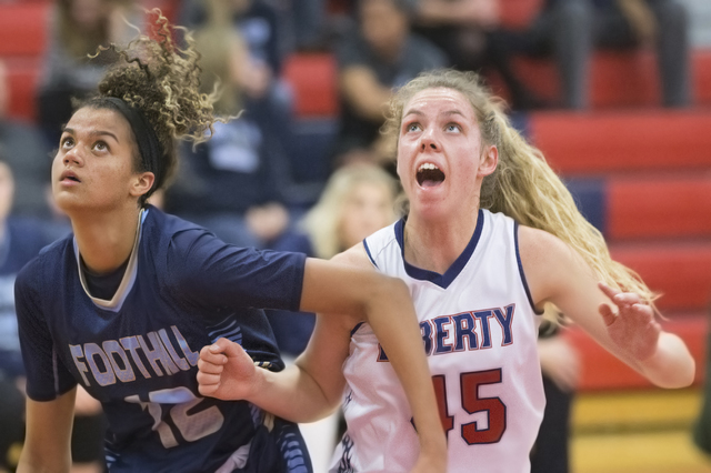 Liberty's Amanda Pemberton (45) fights for position with Foothills Rae Burrell (12) during the Patriots home matchup with the Falcons on Monday, Jan. 9, 2017, at Liberty High School, in Las Vegas. ...