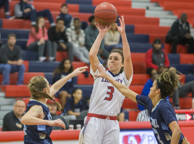 Liberty's Celine Quintino (3) shoots a three point shot over Foothills Rae Burrell (12) and Emily Capps (5) during the Patriots home matchup with the Falcons on Monday, Jan. 9, 2017, at Liberty Hi ...